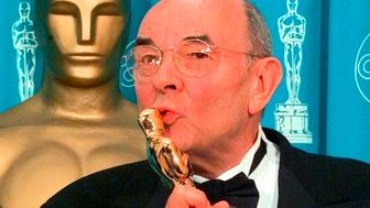 "FILE - In this March 23, 1998 file photo, director Stanley Donen kisses the Oscar he received for Lifetime Achievement backstage at the 70th Academy Awards at the Shrine Auditorium in Los Angeles. Donen, whose ""Singin' in the Rain"" provided some of the most unforgettable moments in movie history, has died, on Thursday, Feb. 21, 2019 in New York.  (AP Photo/Reed Saxon, File)"