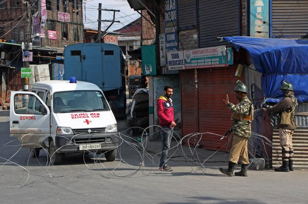 Paramilitary soldiers stop an ambulance driver during restrictions in old city Srinagar, Kashmir on February...