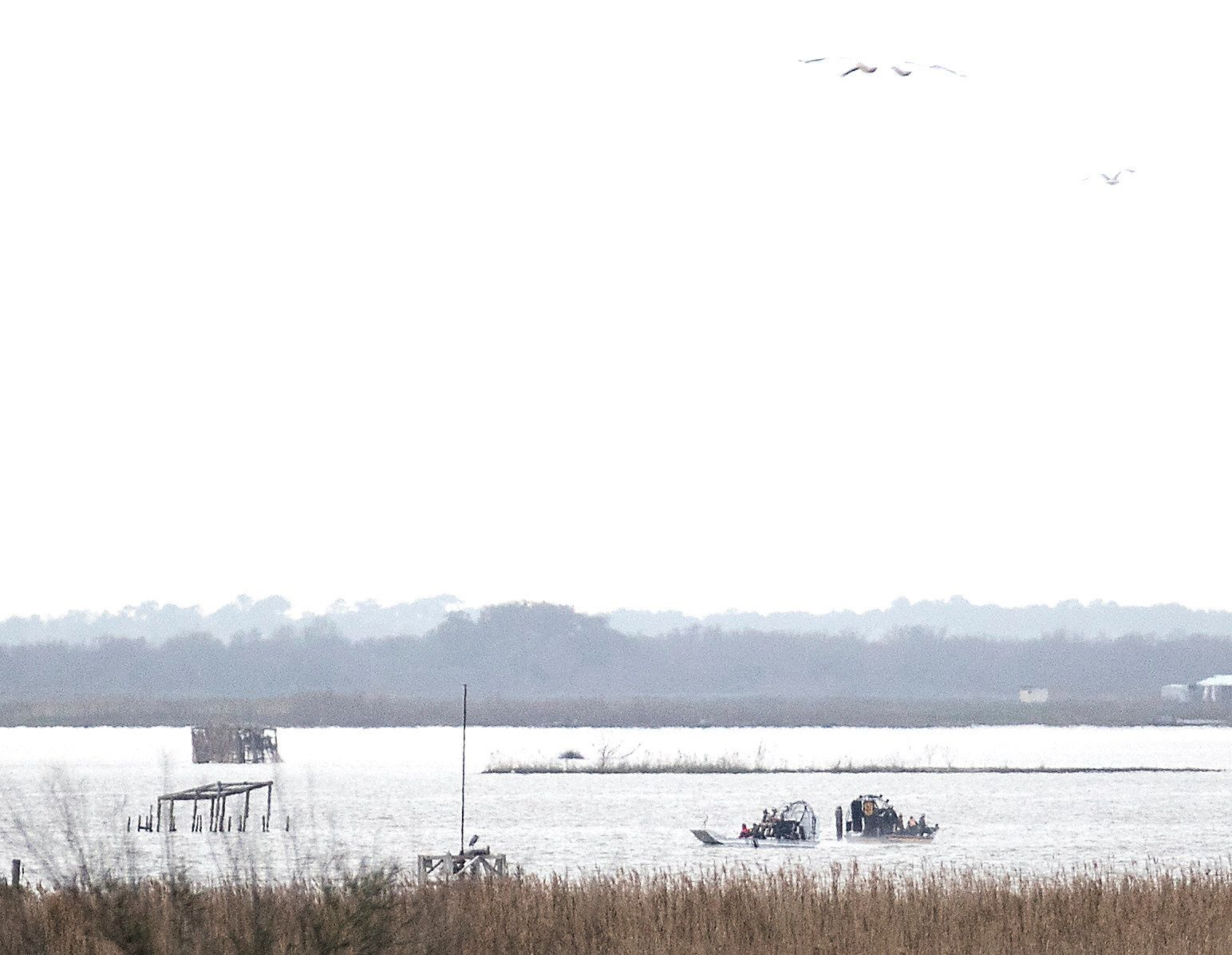 Emergency personnel work at the scene of a plane crash site in Trinity Bay in Anahuac, Texas on Saturday, Feb. 23, 2019. The Federal Aviation Administration said a Boeing 767 cargo plane went down approximately 30 miles southeast of Houston's George Bush Intercontinental Airport. (Brett Coomer/Houston Chronicle via AP)