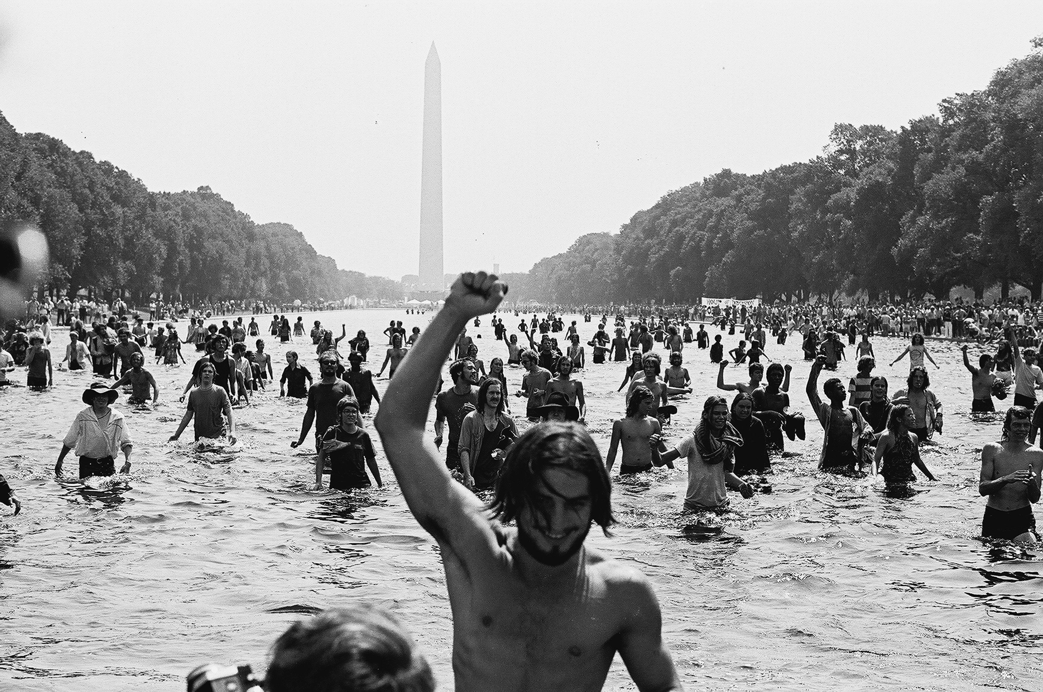 A young American protestor wades shirtless in the Reflecting Pool on the Mall facing away from the Washington Monument during the 'Honor America Day Smoke-In' thrown by marijuana activists to protest the official 'Honor America Day' ceremonies being held at the Lincoln Memorial, Washington, DC, July 4, 1970. (Photo by David Fenton/Getty Images)
