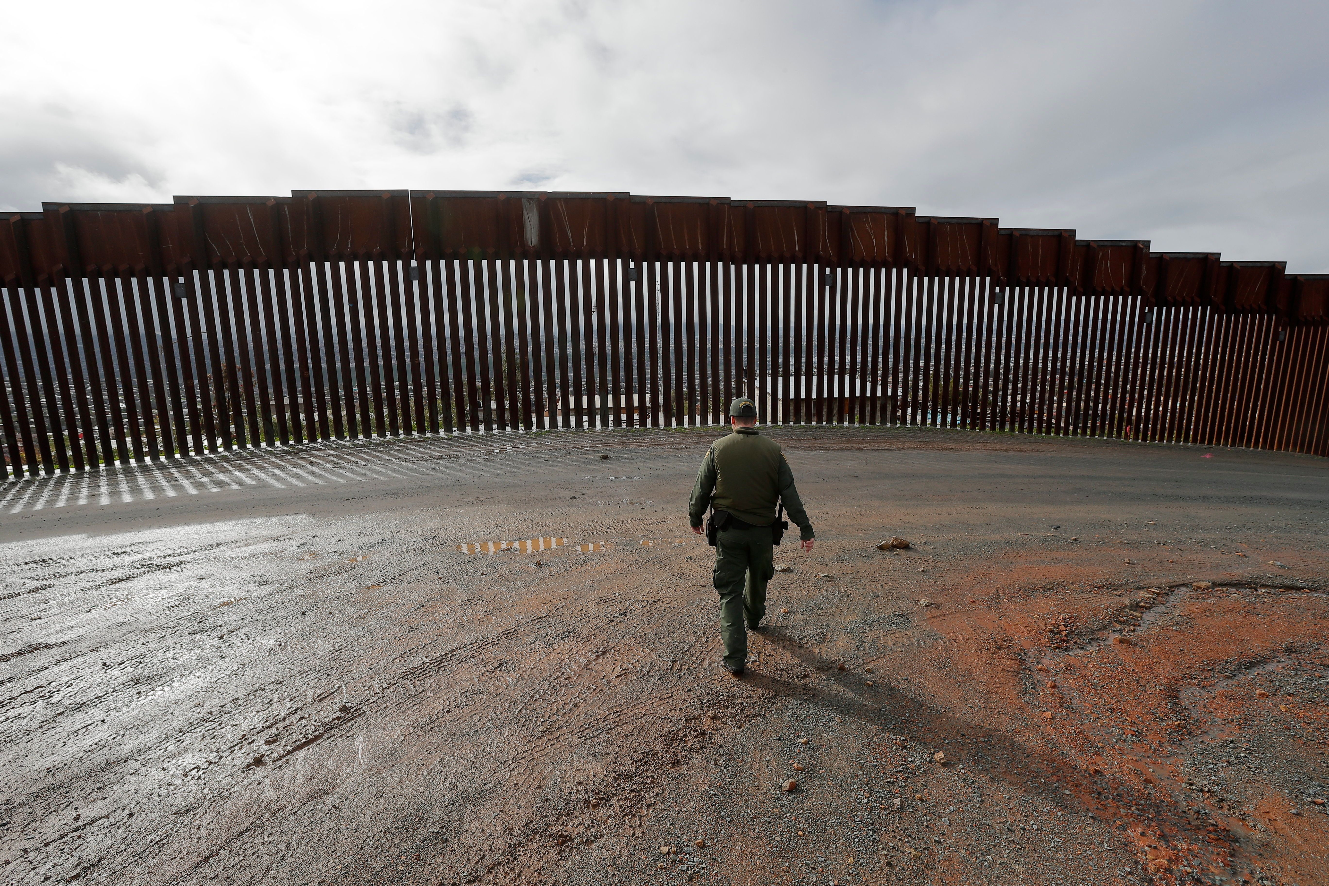 Border Patrol agent Vincent Pirro looks on near a border wall that separates the cities of Tijuana, Mexico, and San Diego, Tuesday, Feb. 5, 2019, in San Diego. President Donald Trump is expected to speak about funding for a wall along the U.S.-Mexico border during his State of the Union address Tuesday. (AP Photo/Gregory Bull)