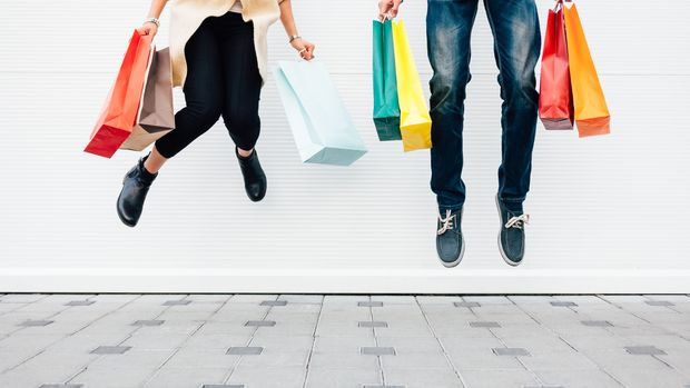 Closeup of woman and man jumping with shopping bags. Shopping concept with copy space.