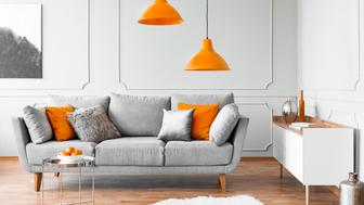 Two orange lamps above grey scandinavian couch with pillows