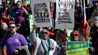FILE - In this Thursday, Feb. 21, 2019 file photo, teachers, students and supporters rally at Frank Ogawa Plaza in front of City Hall in Oakland, Calif. Teachers in Oakland are preparing to strike for a third day after negotiations with the school district broke down over the weekend. (AP Photo/Jeff Chiu, File)