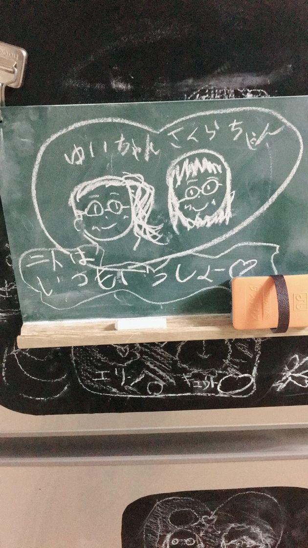 姪がボードに描いてくれた2人の絵。名前と共に「二人はいつもいっしょ♡」と言葉が添えられている
