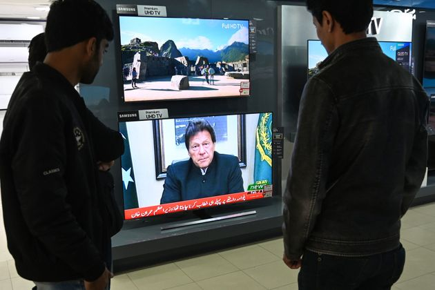 Pakistani people watch the television as Prime Minister Imran Khan speaks to the nation about the suicide...