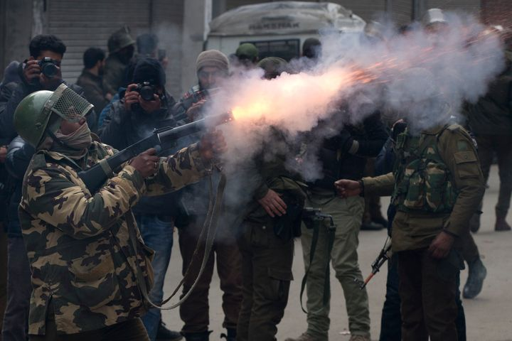 An Indian paramilitary solider fires tear gas shell towards Kashmiri protesters in Srinagar, Indian controlled Kashmir, Tuesd