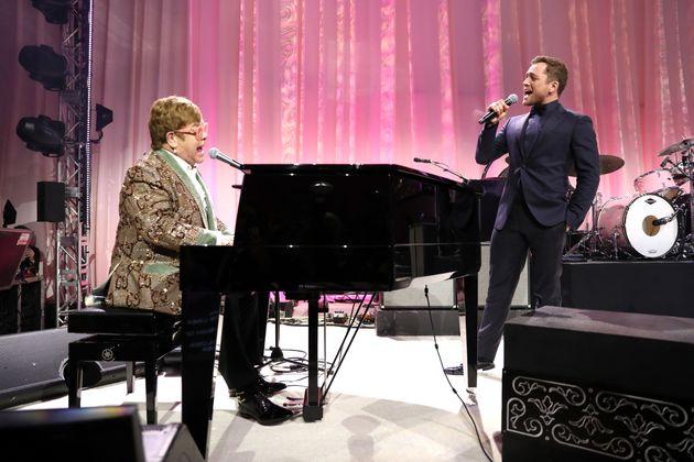 Elton John e Taron Egerton, biografado e ator que o interpreta no cinema cantam juntos o clássico...