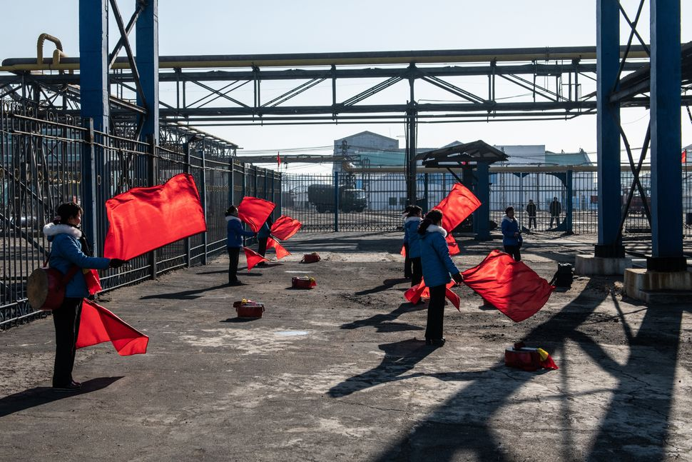 Female workers practice choreographed flag-waving in Hungnam Fertilizer Complex on Feb. 4 in Hamhung, North Korea.