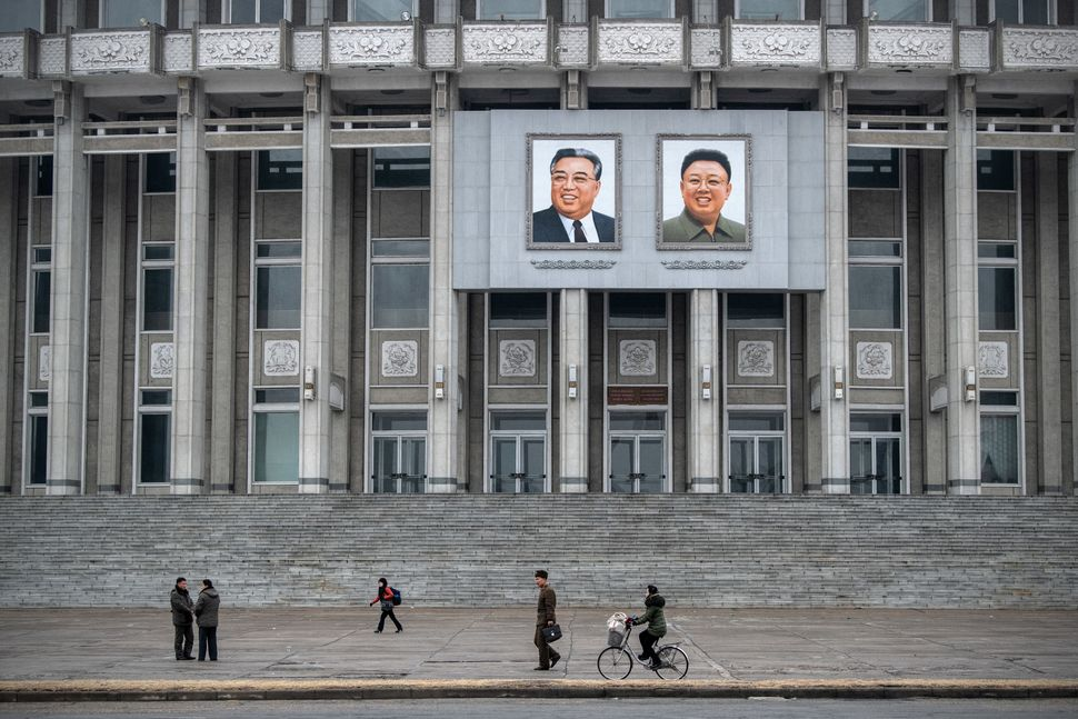 Portraits of Kim Il Sung and Kim Jong Il hang from Hamhung Grand Theatre as people pass on Feb. 3, in Hamhung, North Korea.