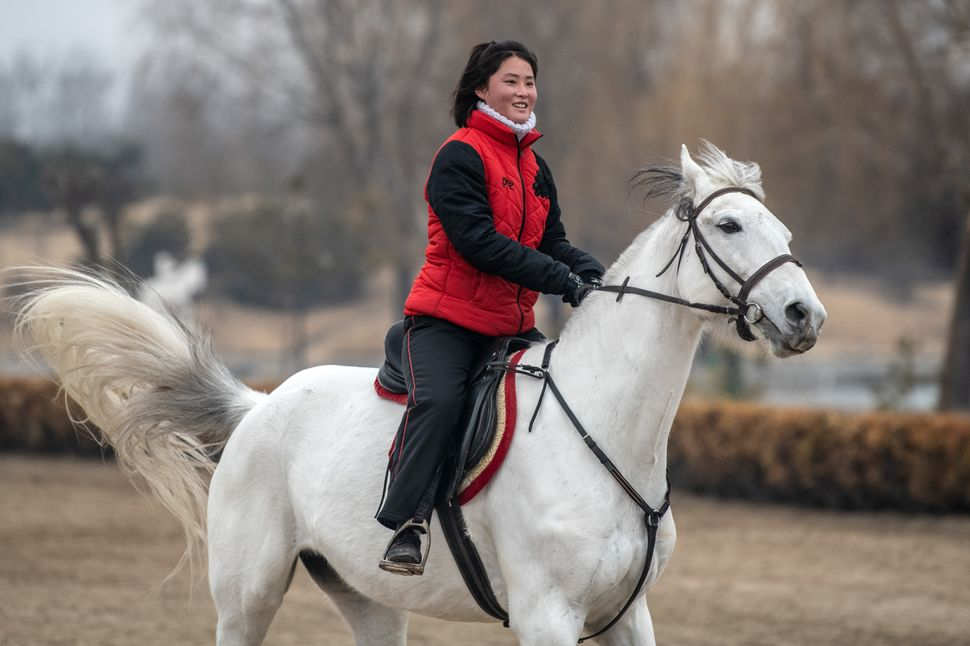 A horseback riding instructor gallops during a break between lessons at Myrim Riding Club on Feb. 6, in Pyongyang.
