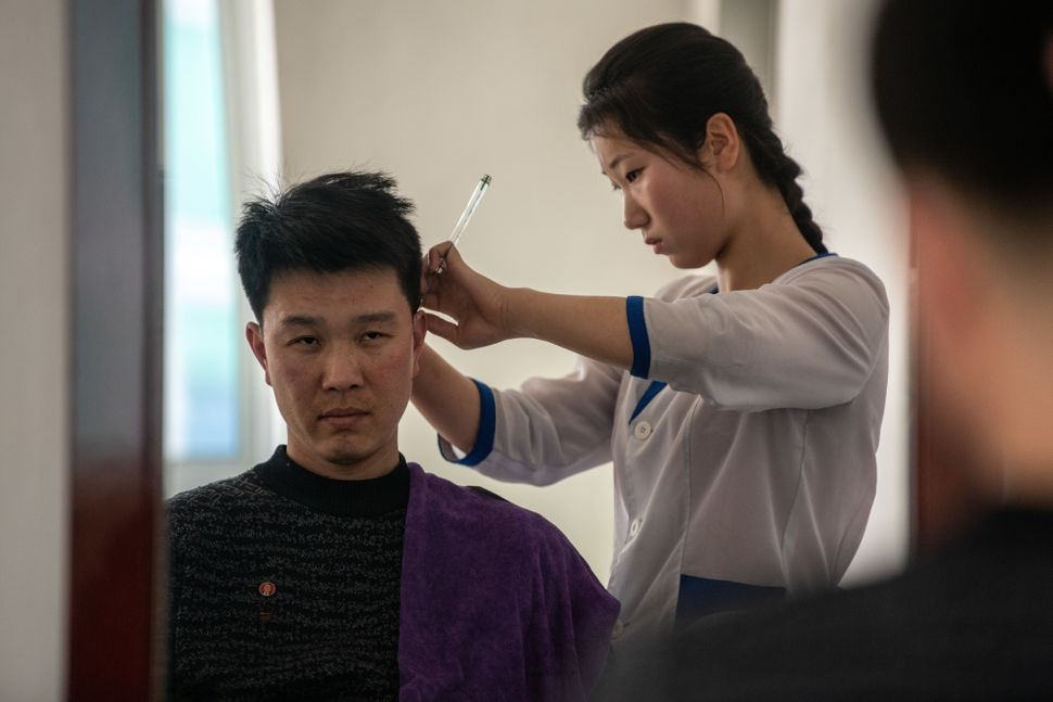 A worker has his hair cut in a salon in Hungnam Fertilizer Complex on Feb. 4, in Hamhung, North Korea.