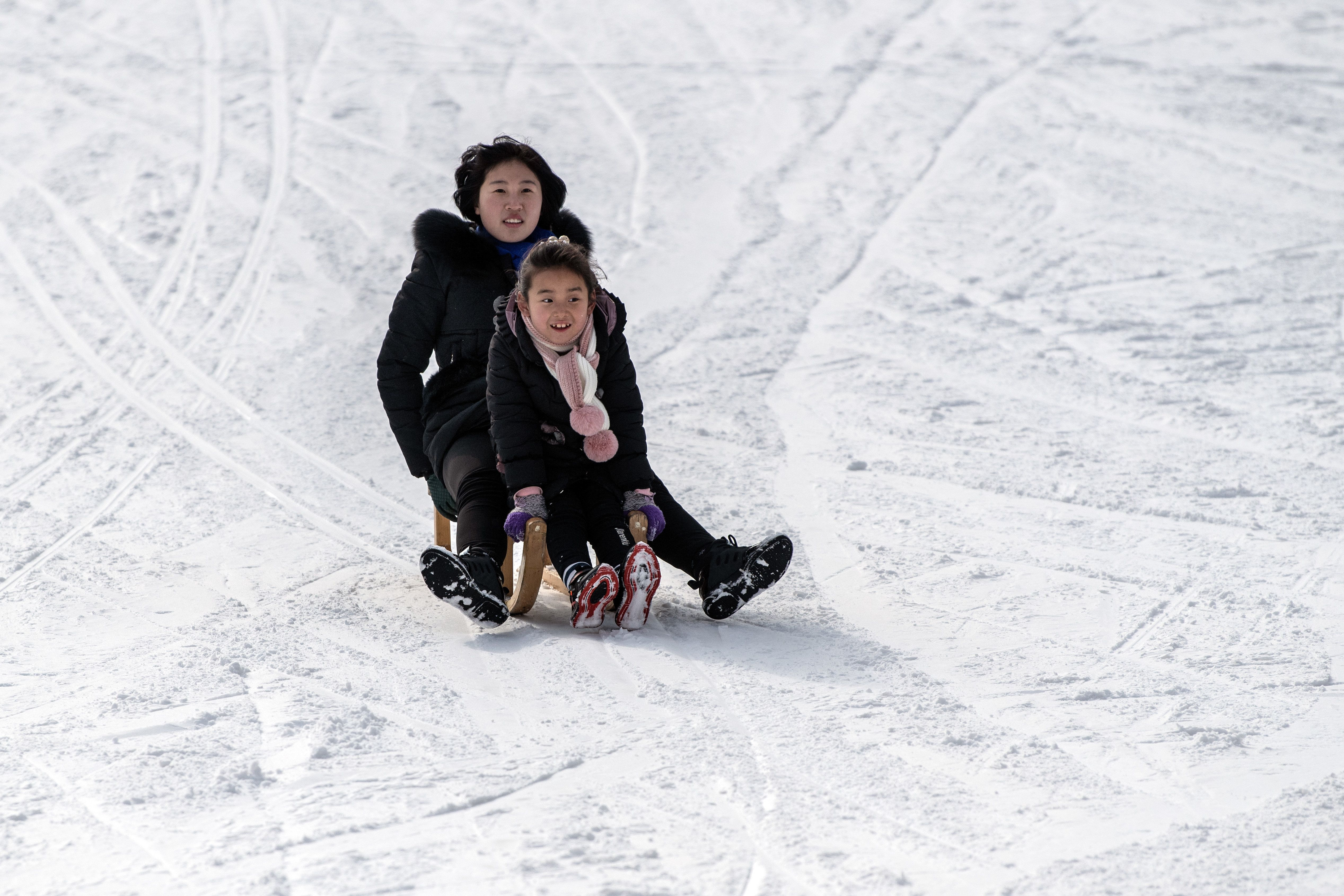WONSAN, NORTH KOREA - FEBRUARY 05: A North Korean woman and child ride a sled on a lower slope at Masikryong Ski Resort on February 05, 2019 near Wonsan, North Korea. U.S President Donald Trump and North Korean Supreme Leader Kim Jong Un will hold a second summit in the Vietnamese capital of Hanoi later this month following a historic summit in Singapore last June. Although the two countries remain technically at war and with negotiations surrounding the details of North Korea's nuclear disarmament continuing, President Trump has hailed Kim Jong Un and North Korea with a tweet in which he predicted that the country would become 'a great economic powerhouse' thanks to Mr Kim's leadership. (Photo by Carl Court/Getty Images)