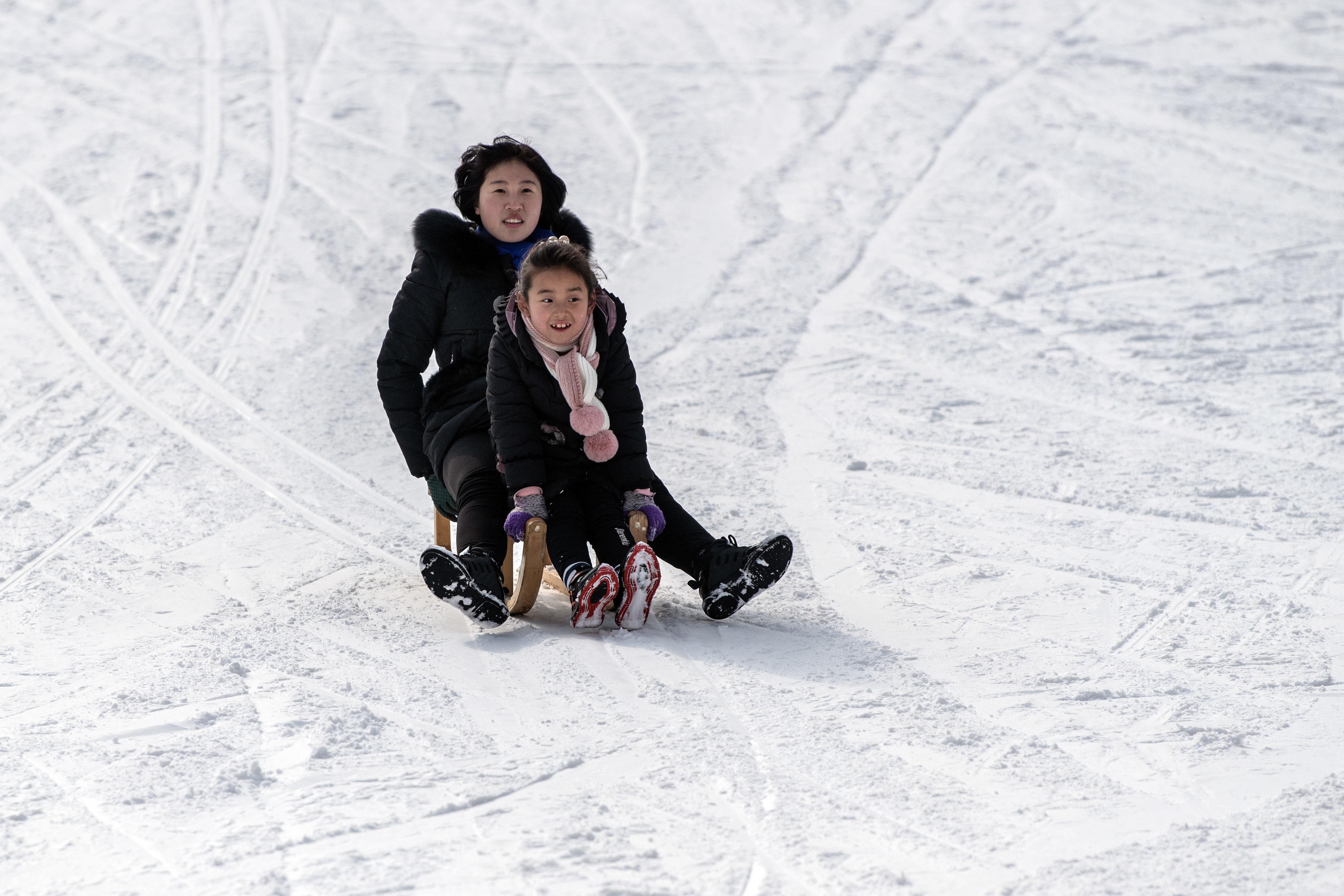 A North Korean woman and child ride a sled on a lower slope at Masikryong Ski Resort on Feb. 5, near Wonsan, North Korea.