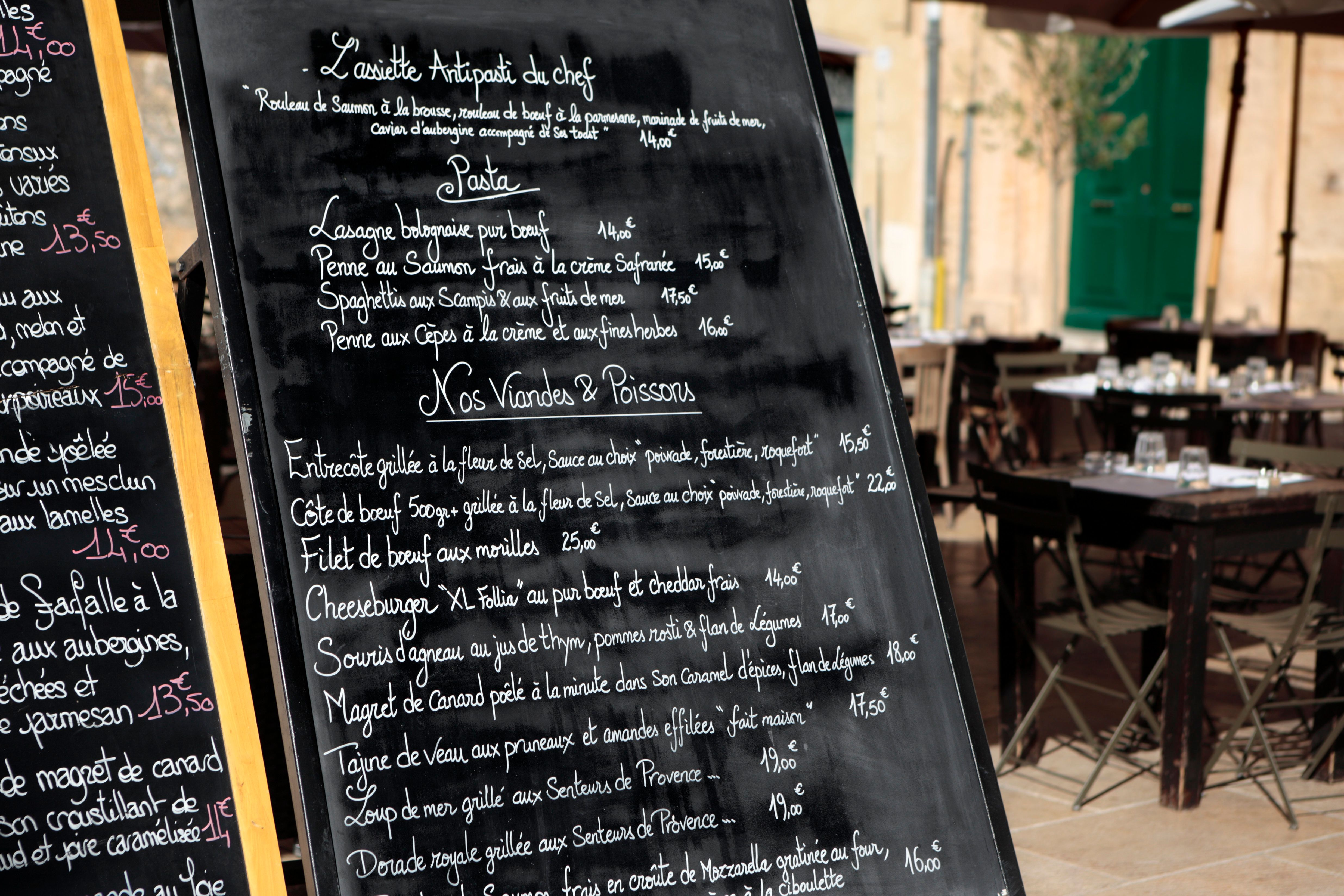 Restaurant in France with menus.  Focus on the menus with tables and chairs in the background blurred.You might also like this atmospheric cafe scene: