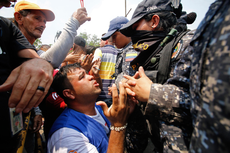 A supporter of Venezuela's opposition leaderJuan Guaidó demonstrates in front of members of Venezuela's Bolivari