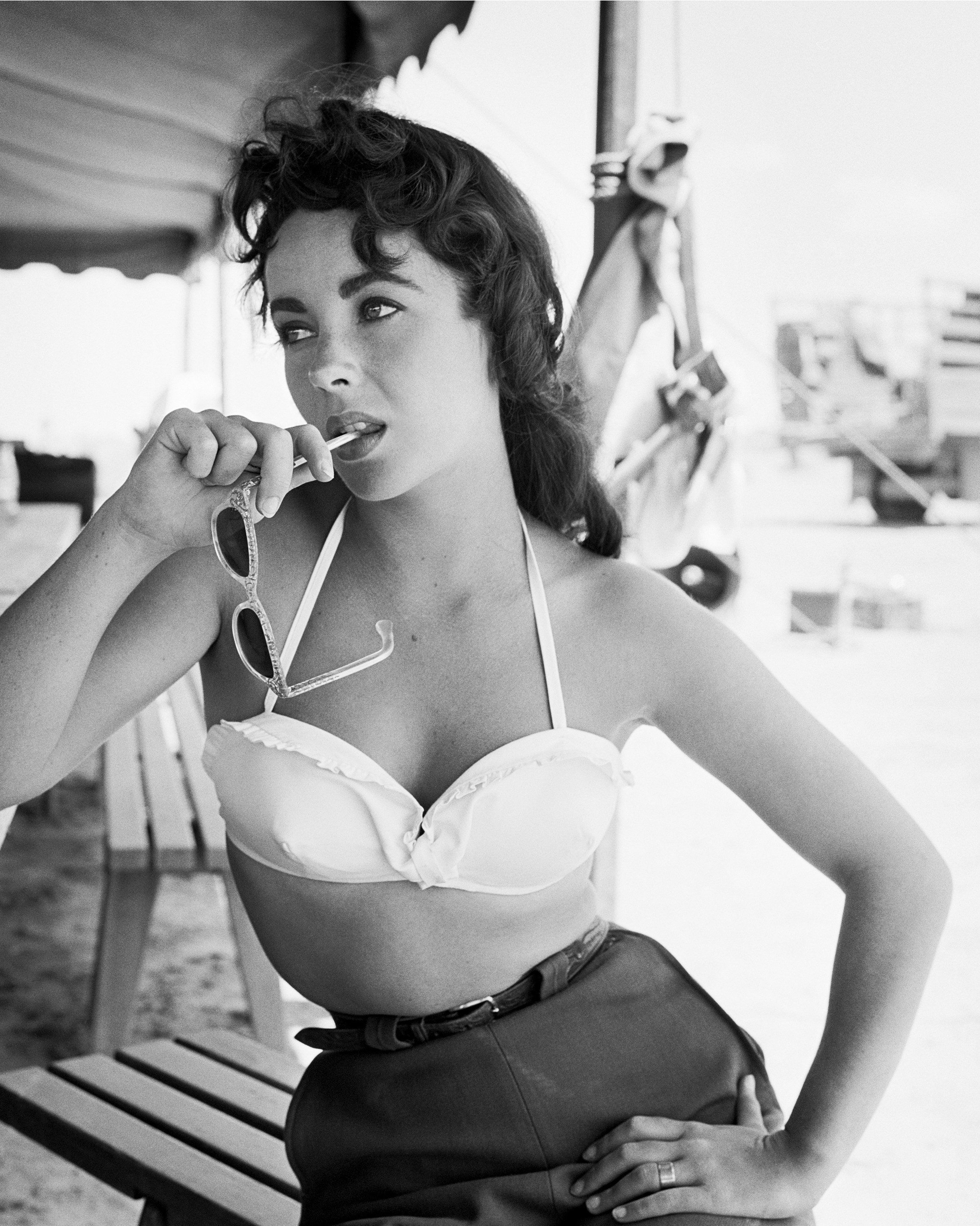 NOVEMBER 24: Actress Elizabeth Taylor teases with sunglasses in her mouth as she poses on the set of the movie 'Giant' which was released on November 24, 1956. (Photo by Frank Worth, Courtesy of Capital Art/Getty Images)