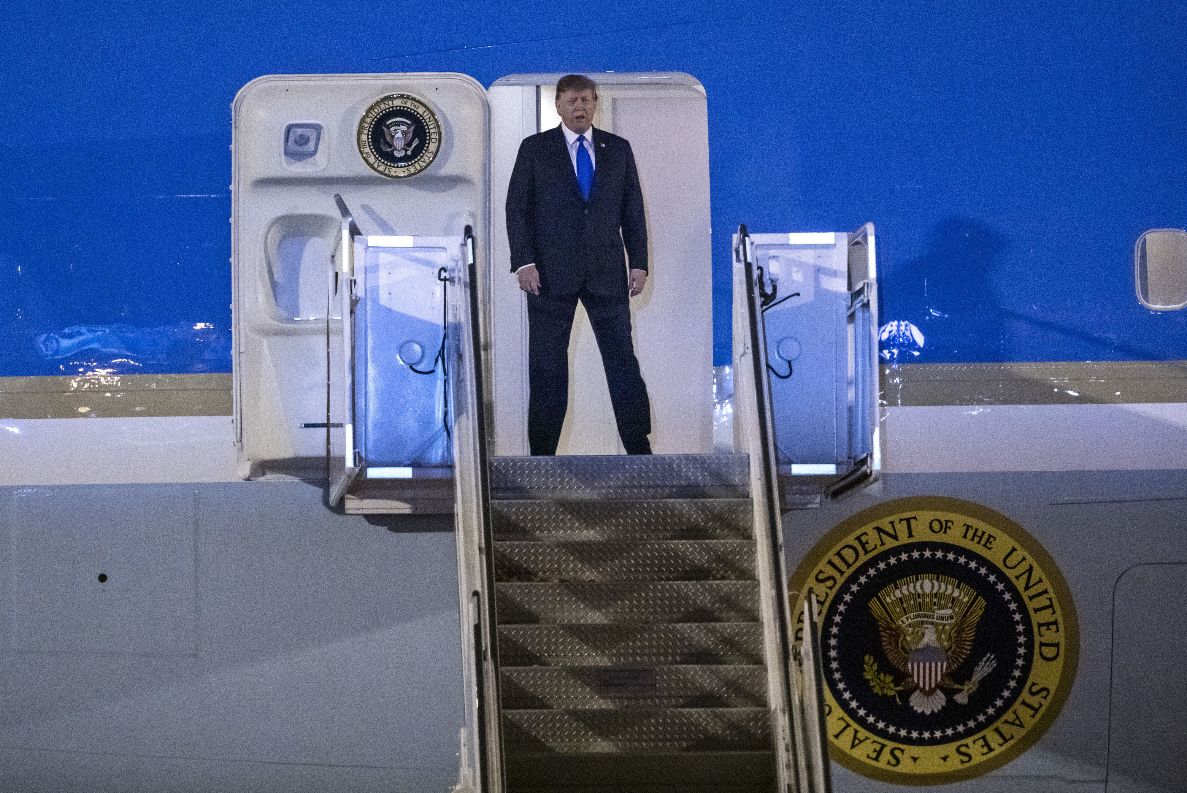 U.S. President Donald Trump disembarks from Air Force One after arriving at Noi Bai International Airport in Hanoi, Vietnam, on Tuesday, Feb. 26, 2019. The slapdash nature of Trumps second summit with Kim Jong Un was exposed on Tuesday, as American journalists were abruptly evicted from a Hanoi hotel housing the North Korean leader and key details of the meeting remained a mystery. Photographer: Justin Chin/Bloomberg via Getty Images