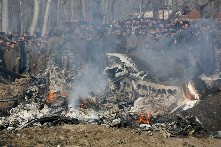 Kashmiri villagers gather near the wreckage of an Indian aircraft after it crashed in Budgam area, outskirts of Srinagar, Ind
