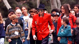 Pop star Michael Jackson and Lisa Marie Presley walk with children that were invited guests at his Neverland Ranch home, Tuesday, April. 18, 1995, in Santa Ynez, Calif. (AP Photo/Mark J. Terrill)