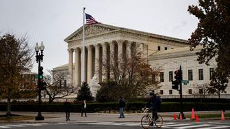 FILE PHOTO: A man rides a bicycle past the Supreme Court in Washington, U.S., November 13, 2018. REUTERS/Al Drago/File Photo