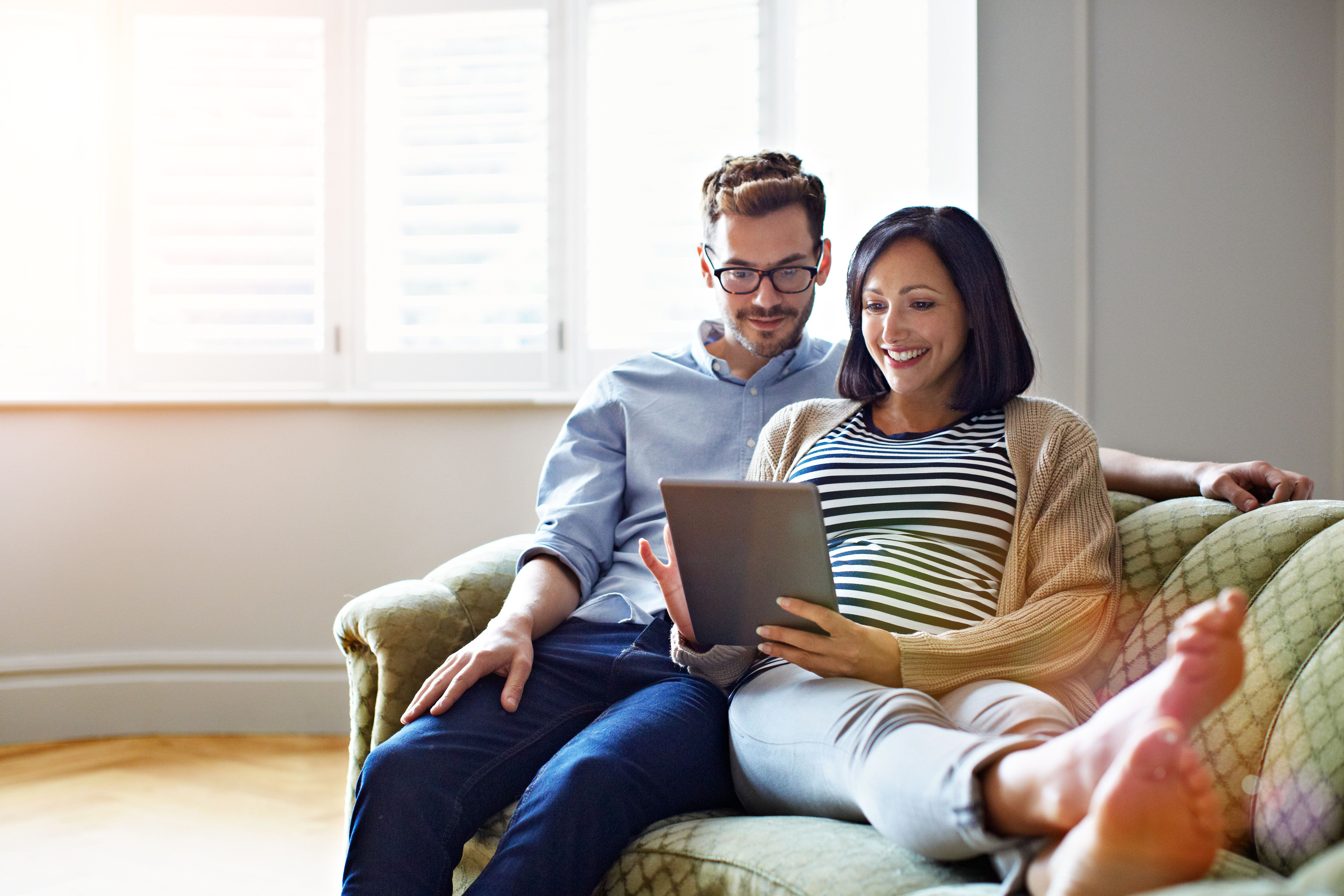 Shot of a pregnant woman and her husband sitting on their sofa using a digital tablet