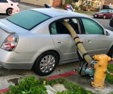 """This Feb. 26, 2019 photo provided by the Anaheim Fire and Rescue shows a car with a firehose running through the rear side windows in Anaheim, Calif. A California fire department enflamed some social media users but delighted others by posting pictures of the busted-out windows of a car that parked in front of a fire hydrant. In a Twitter thread posted Wednesday, the Anaheim Fire Department asked the public: """"Ever wonder what happens when a car is parked in front of a fire hydrant and a fire breaks out."""" (Anaheim Fire and Rescue via AP)"""