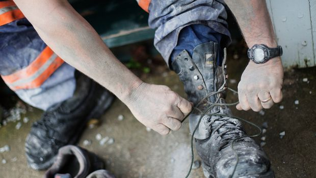 """In this Oct. 20, 2014 photo, third generation coal miner Keith Johnson takes off his boots as he arrives home after working the graveyard shift underground in a coal mine in Evarts, Ky. Johnson has managed to keep mining in Harlan County. But it's been a struggle. In the past two years, he's been laid off from one coal company, then moved to another, only to have it close when a long-term contract expired. At 43, he's gone from being a foreman making about $100,000 a year to a common miner at $20 an hour. """"A few years ago I would have said we'd live a long life here,"""" says Johnson. """"But its dim, there's just not enough money to sustain your family here. It's a bleak outlook."""" (AP Photo/David Goldman)"""