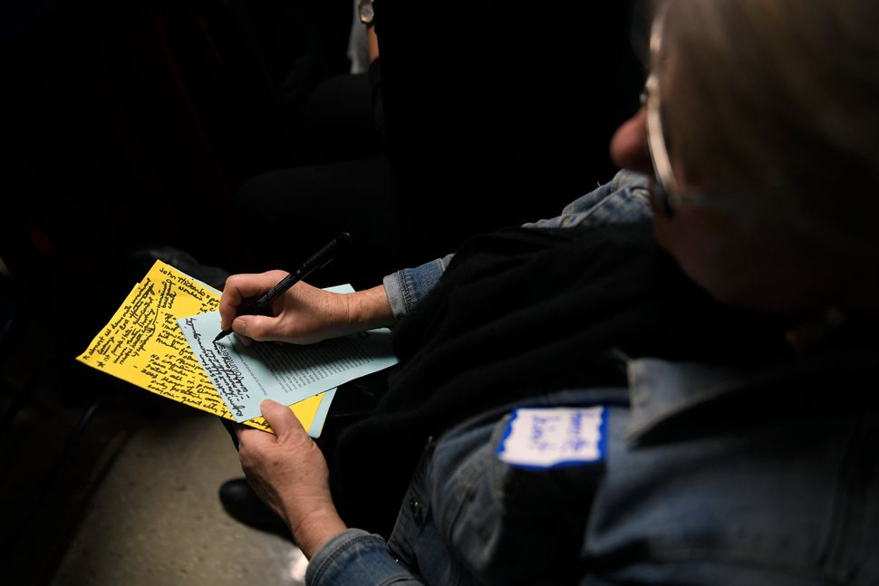 Ammertte Deibert, 70, of Ames, Iowa, jots down notes as she listens to Harris, former Colorado Gov. John Hickenlooper and for