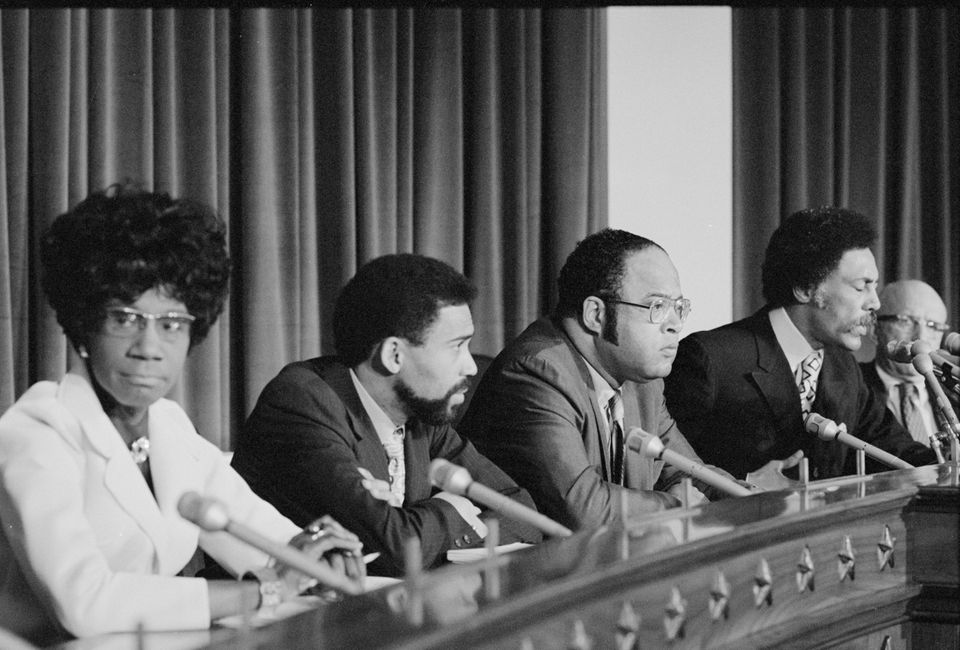 Members of the original Congressional Black Caucus sit on the Congressional dais in
