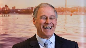 Washington Gov. Jay Inslee smiles as he takes a turn speaking during a joint news conference with British Columbia Premier John Horgan Thursday, Feb. 7, 2019, in Seattle. The two met earlier in the day to discuss regional issues and opportunities for collaboration between B.C. and Washington state. (AP Photo/Elaine Thompson)