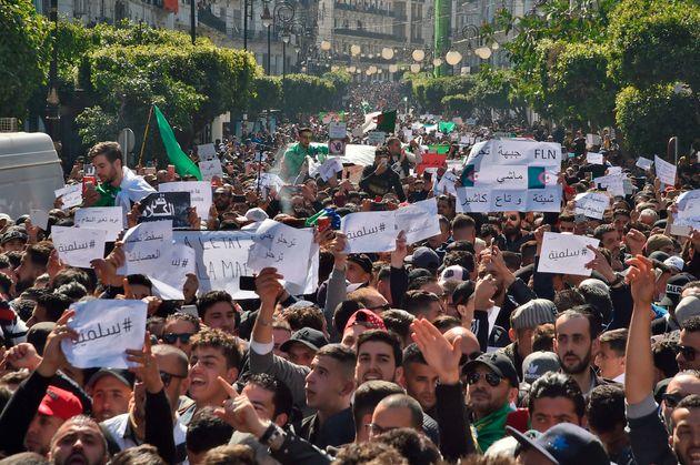 Des Algériens manifestent en tenant des papiers sur lesquels on peut lire