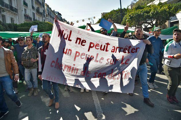 Des jeunes protestent avec une banderole sur laquelle on peut lire: