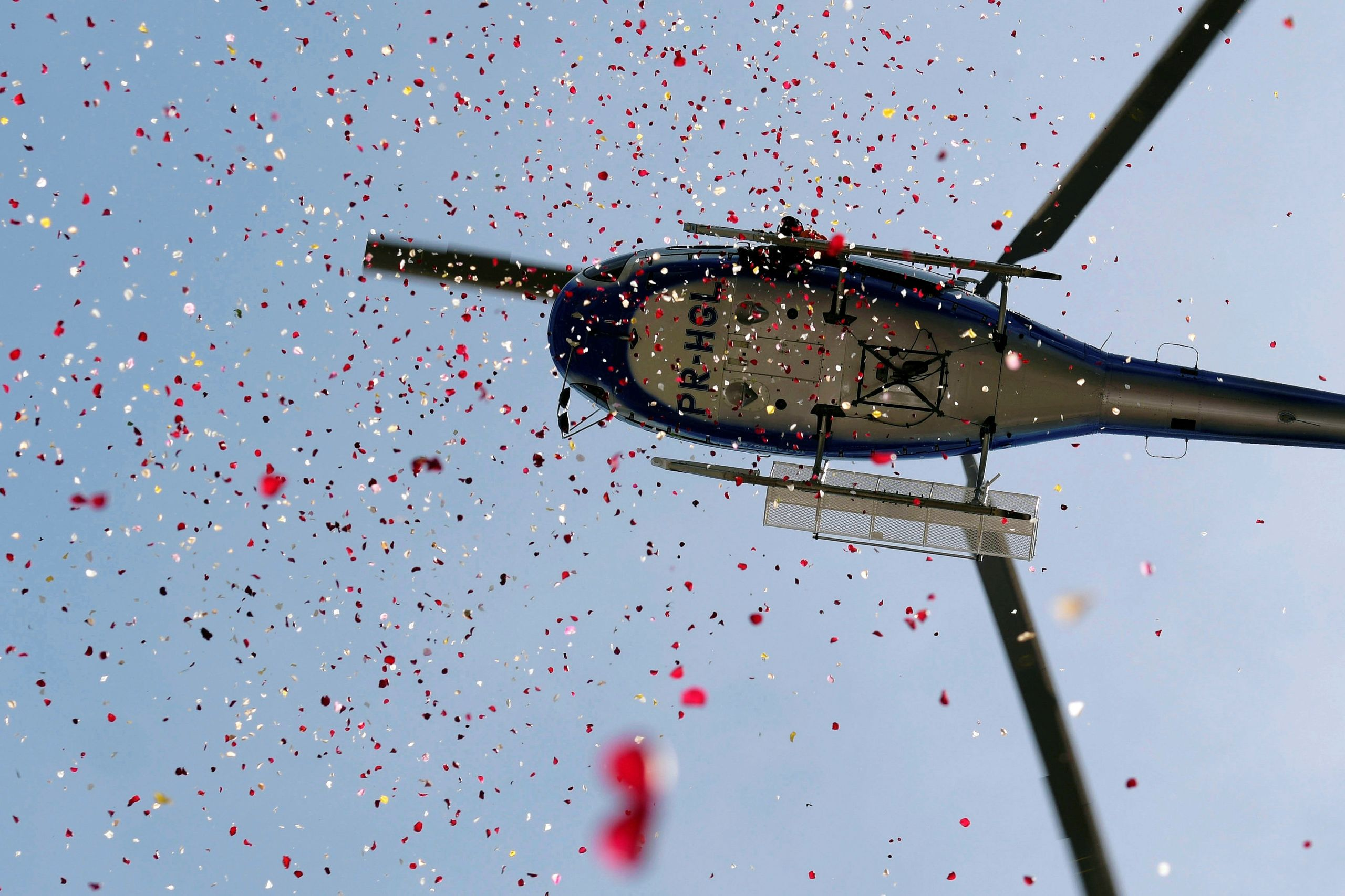 A helicopter showers flowers in honor of victims of the collapse of a dam owned by Brazilian mining company Vale SA, in Bruma
