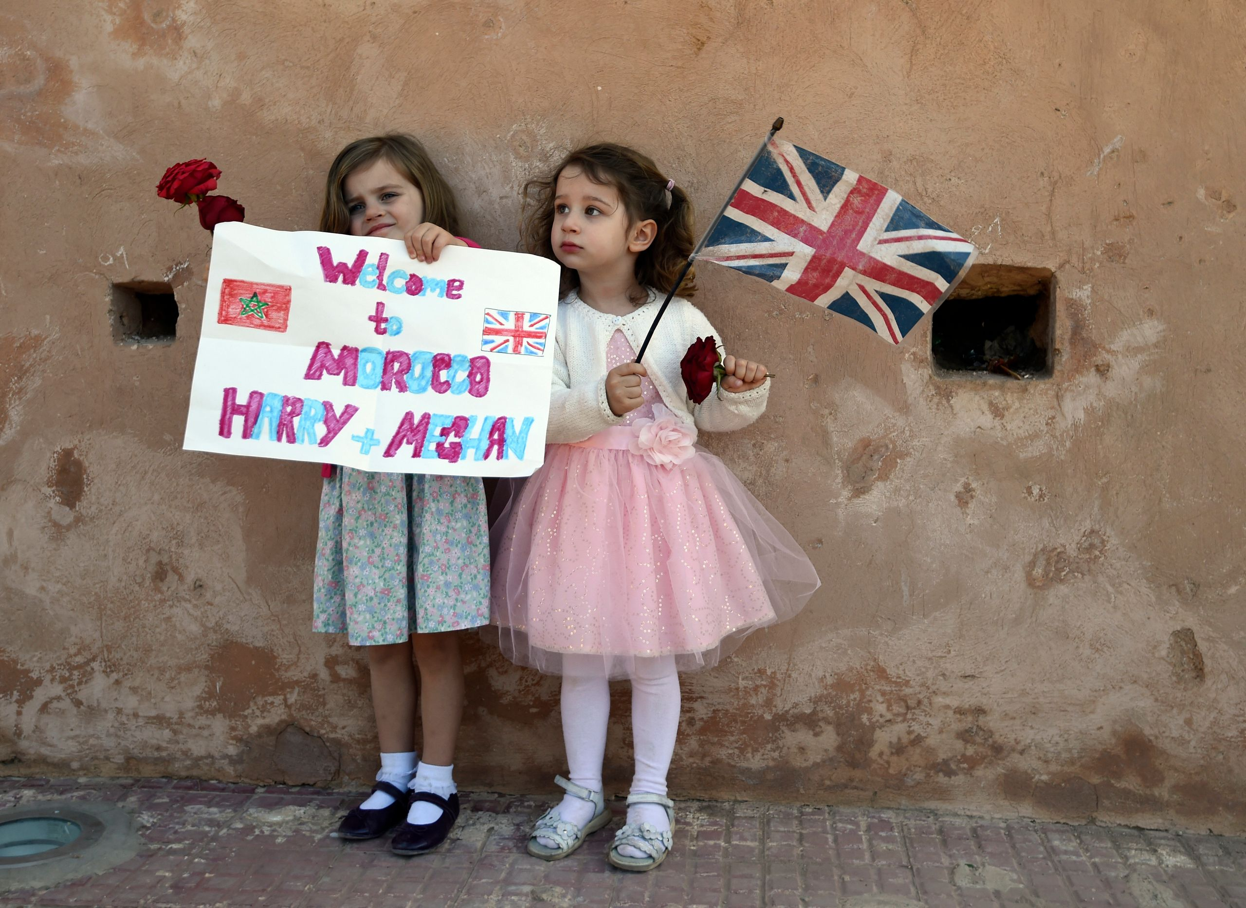 Children wait for the arrival of Britain's Prince Harry and Meghan, Duchess of Sussex, at the Andalusian Gardens in Rabat, Mo