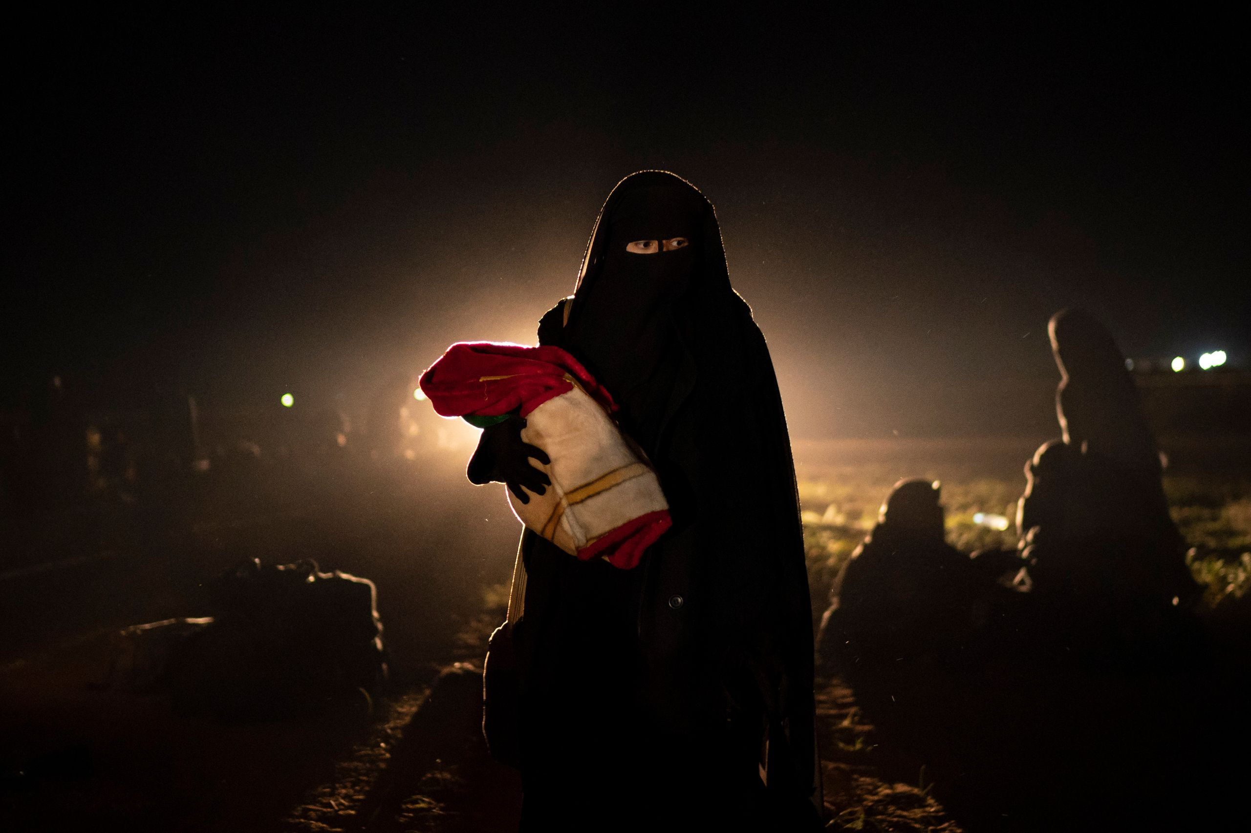 A woman who was evacuated out of the last territory held by Islamic State militants holds her baby after being screened by U.