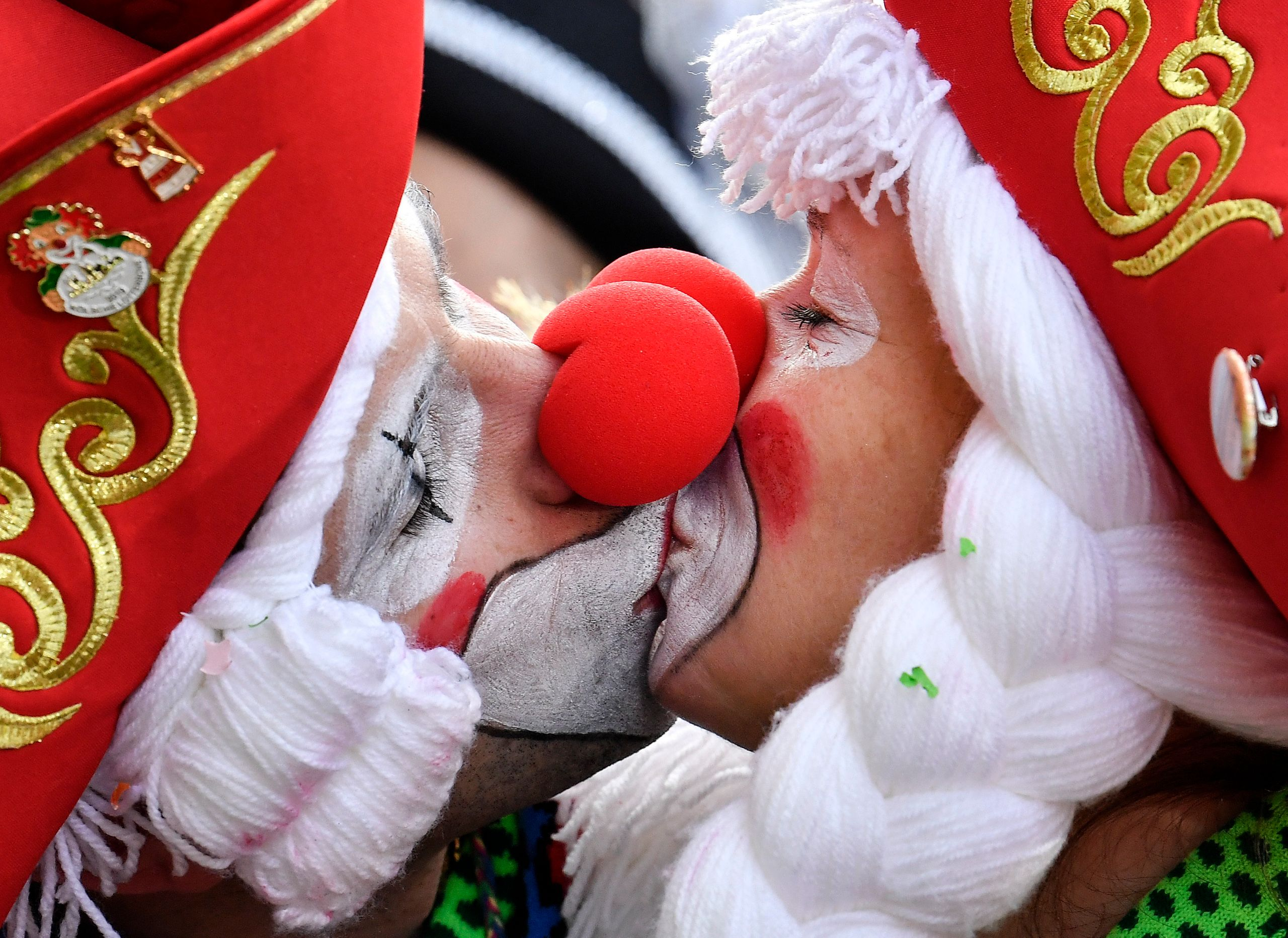 Two revelers kiss for photographers as thousands dressed in costumes celebrate the start of the street carnival in Cologne, G