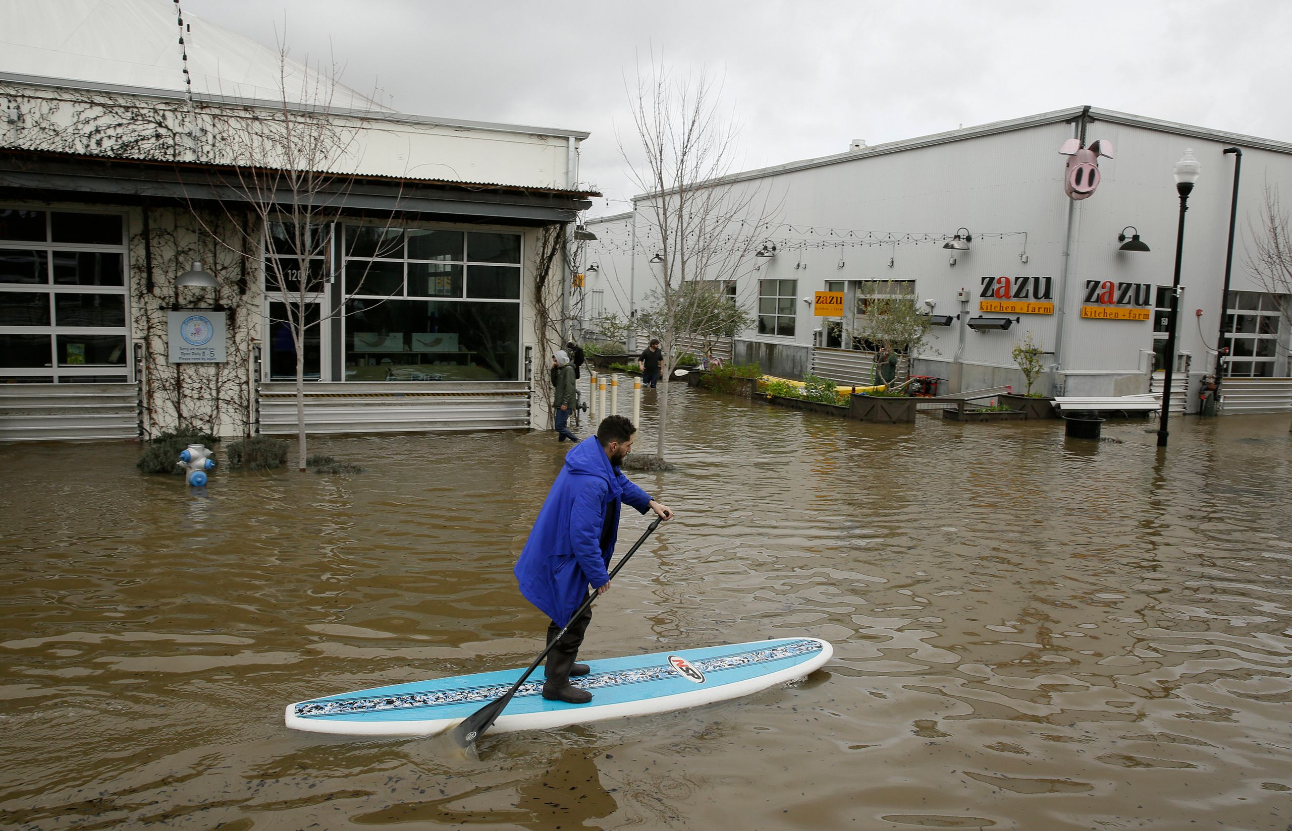 A man uses a paddleboard to make his way through the flooded Barlow Market District on Feb. 27, 2019, in Sebastopol, Californ