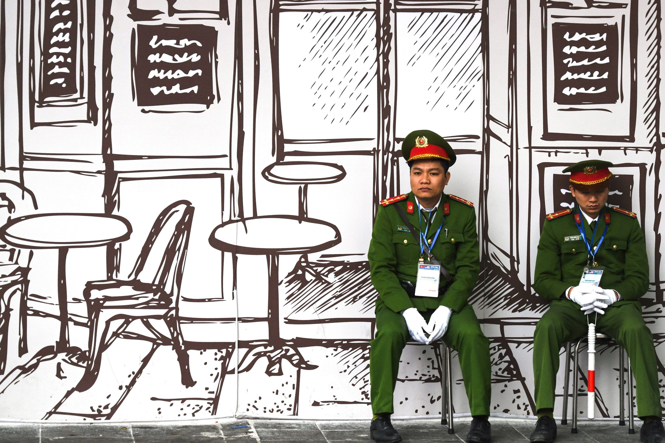 Vietnamese police sit on stools near the Sofitel Legend Metropole hotel in Hanoi on Feb. 27, 2019, ahead of the second U.S.-N