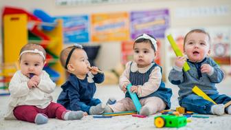 Group of toddlers sitting indoors in a daycare center. They are playing with colorful wooden blocks. Some of the kids are putting the blocks in their mouths.