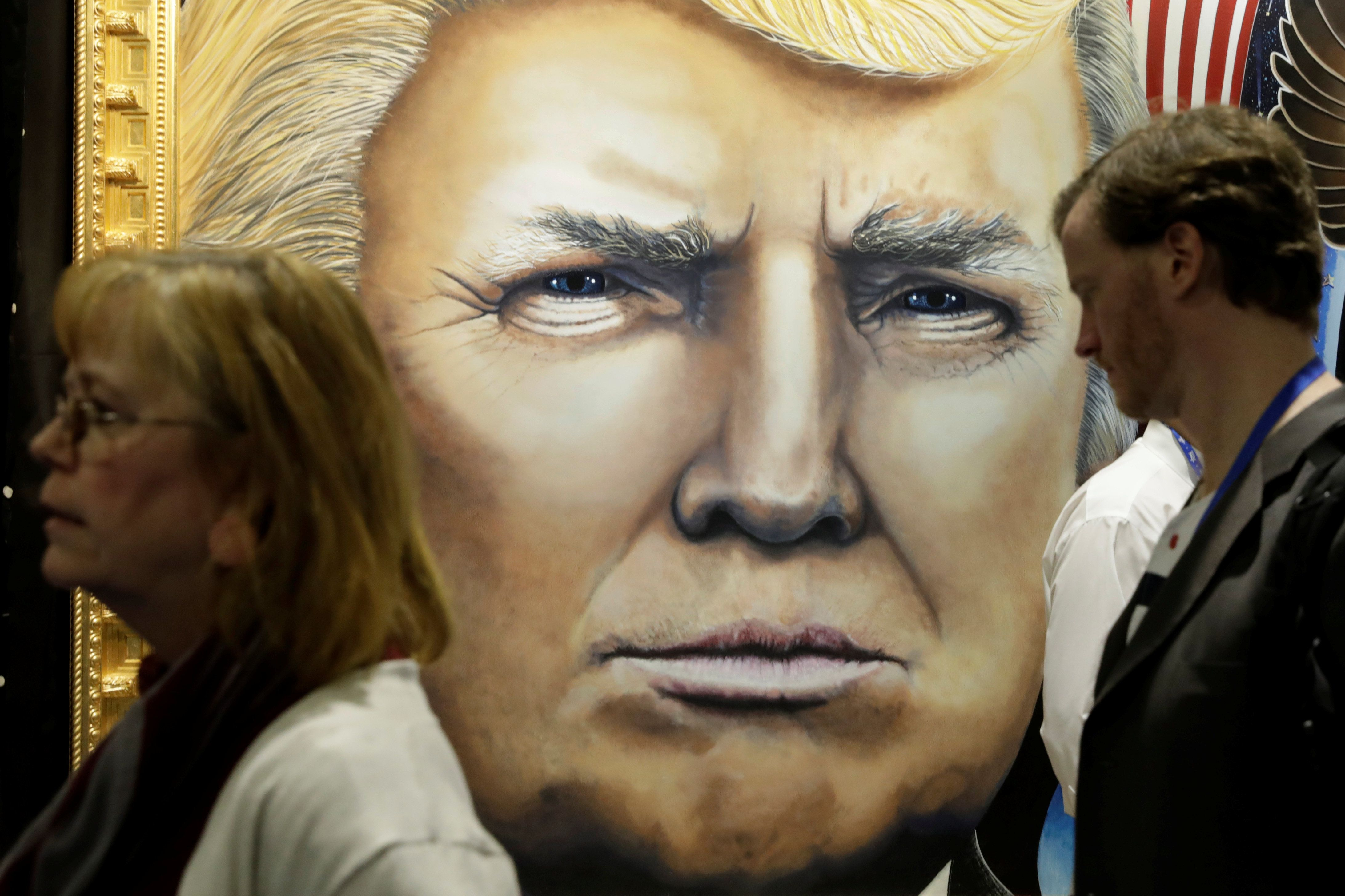 Attendees walk past a painting of U.S. Donald Trump in an exhibition hall at the Conservative Political Action Conference (CPAC) annual meeting at National Harbor near Washington, U.S., March 1, 2019. REUTERS/Yuri Gripas
