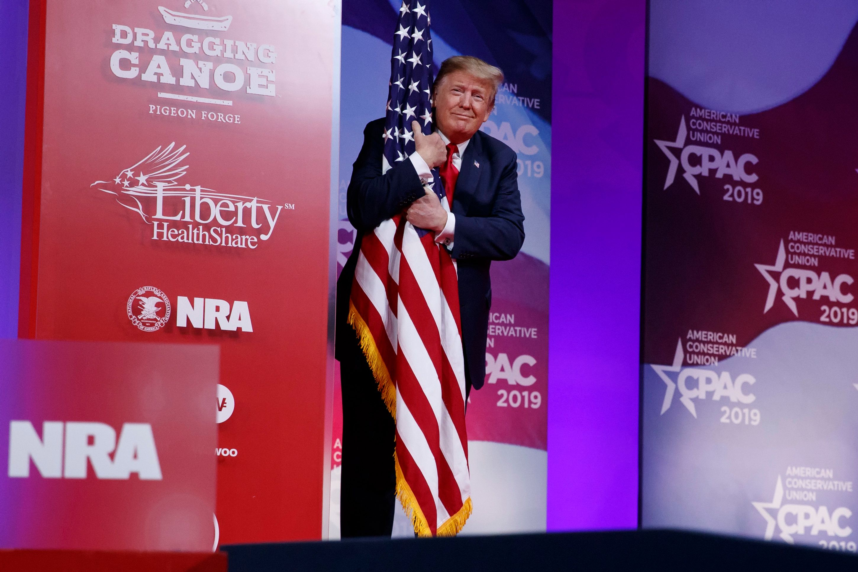 President Donald Trump hugs the American flag as he arrives to speak at Conservative Political Action Conference, CPAC 2019, in Oxon Hill, Md., Saturday, March 2, 2019. (AP Photo/Carolyn Kaster)
