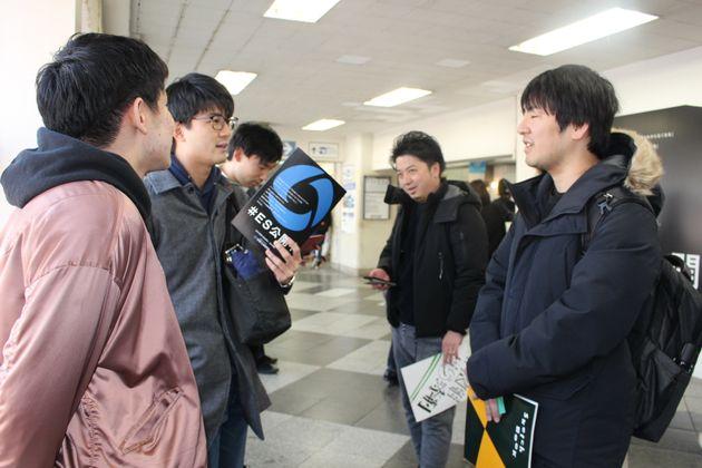大学生と立ち話する流さん(右手前)と三木さん(右奥)