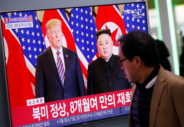 A man watches a TV broadcasting a news report on a meeting between North Korean leader Kim Jong Un and...