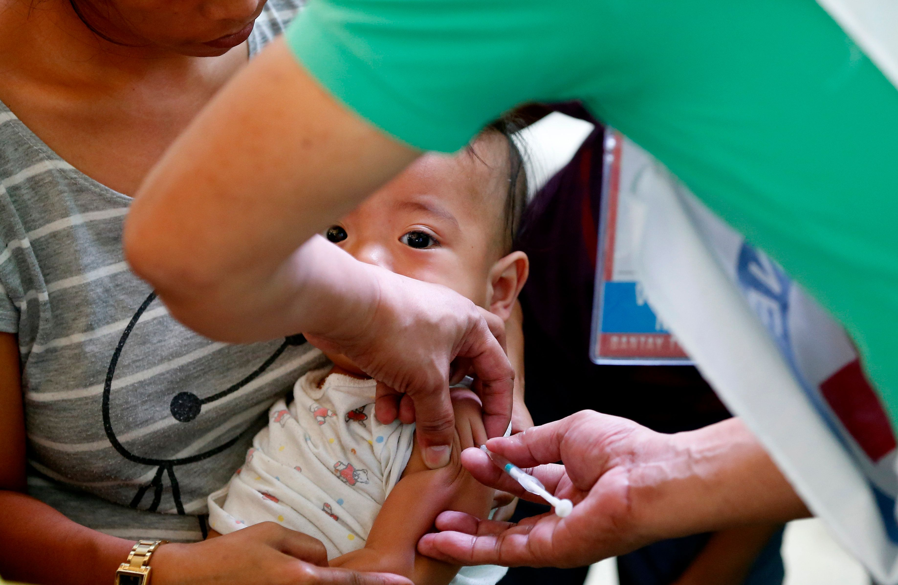 Philippine National Red Cross and Health Department volunteers conduct house-to-house measles vaccination to children at an informal settlers community in Manila, Philippines following an outbreak of measles that already spread to four regions in the country and has claimed the lives of more than five dozen victims Saturday, Feb. 16, 2019. The house-to-house vaccination was prompted by the reluctance of parents to have their children vaccinated due to the controversy involving an anti-Dengue vaccine known as Dengvaxia. In an effort to convince the parents, the Department of Health has tapped the services of President Rodrigo Duterte and Filipino boxing champion and now Senator Manny Pacquiao to allay fearful parents. (AP Photo/Bullit Marquez)