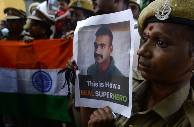 Indian security personnel carrying a picture of Wing Commander Abhinandan Varthaman on the day of...