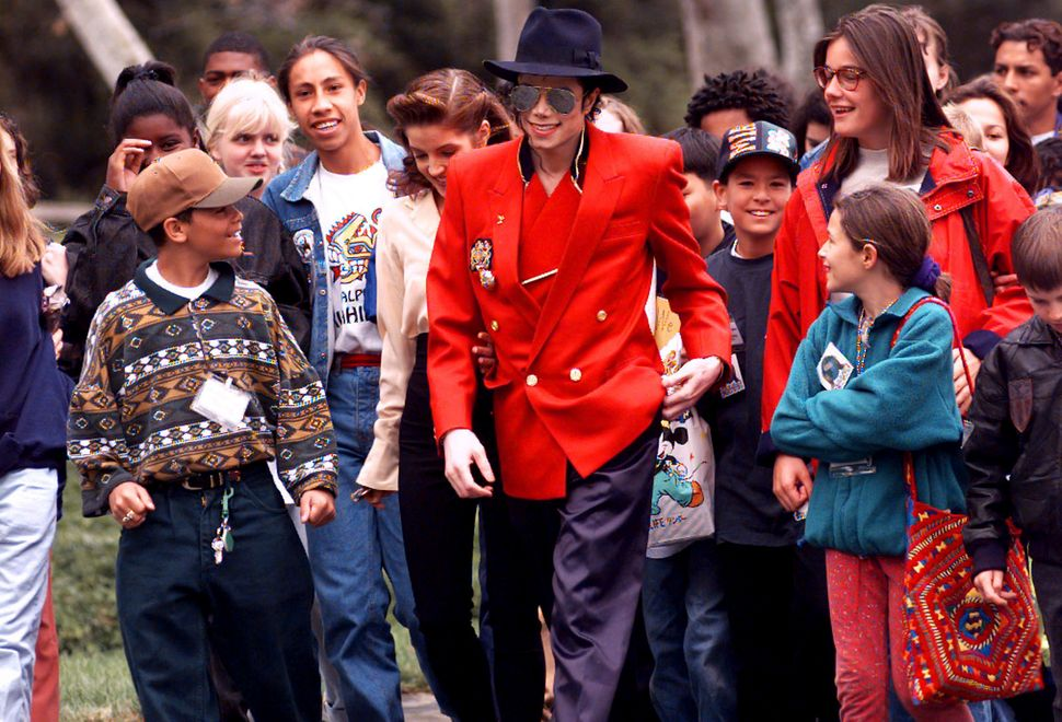 Michael Jackson and his then-wife Lisa Marie Presley, giving children a tour of his Neverland ranch in 1995.