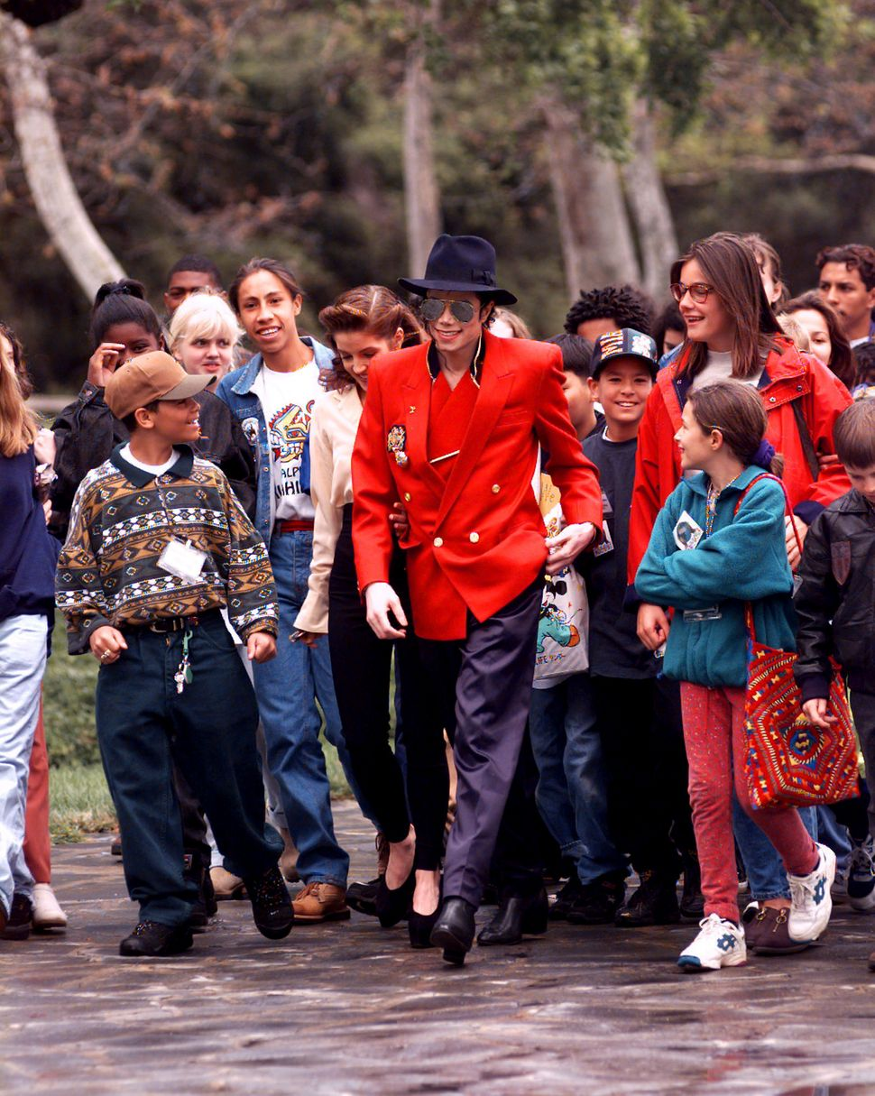 Michael Jackson and his then-wife Lisa Marie Presley, giving children a tour of his Neverland ranch in