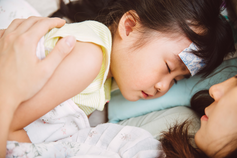 発熱した女の子に寄り添う母親 イメージ写真