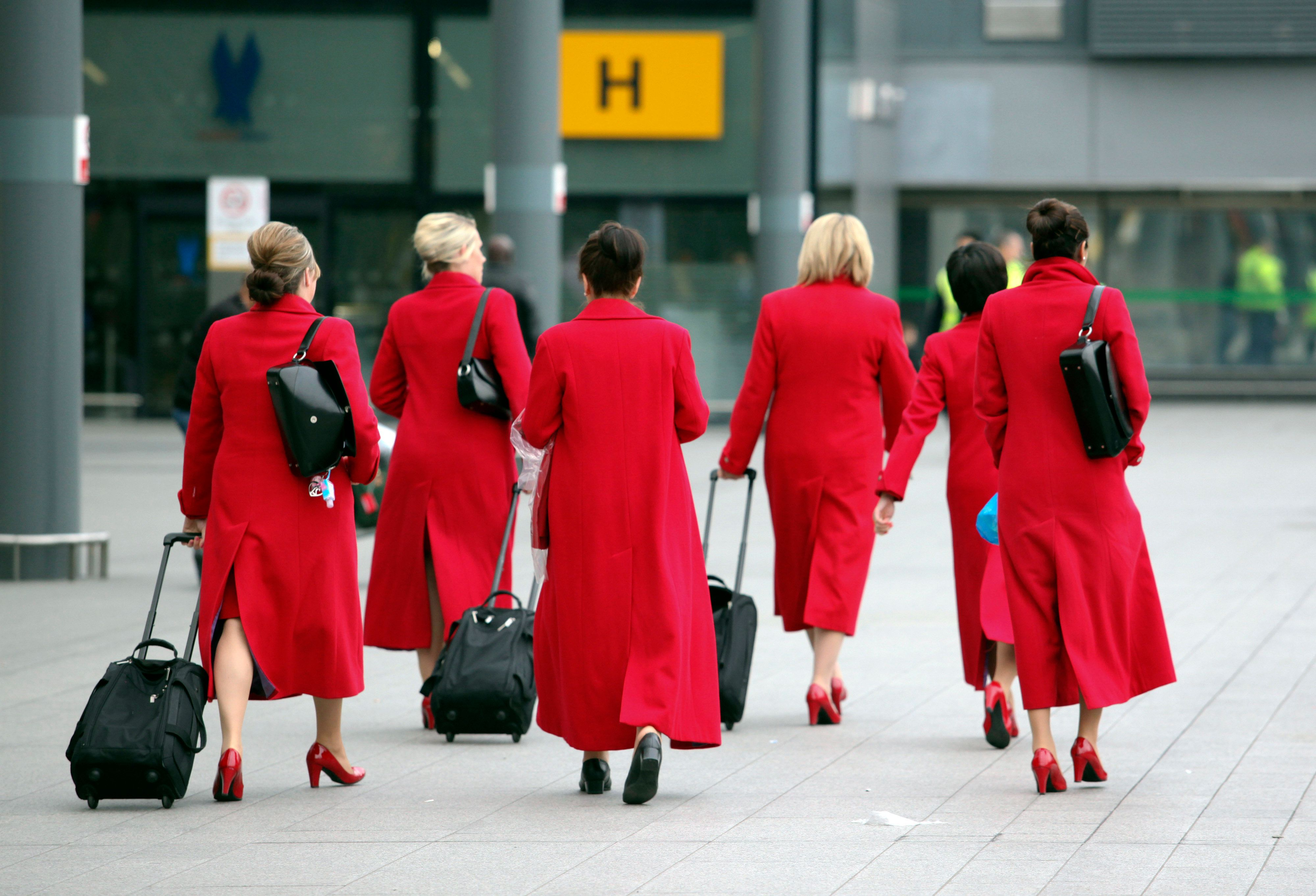 Virgin Atlantic Airways Ltd. cabin crew walk towards Terminal 3 at Heathrow airport, operated by BAA Ltd., in London, U.K., on Wednesday, Jan. 11, 2012. BAA Ltd.'s London Heathrow airport, the busiest in Europe, handled a record 69.4 million passengers last year, pushing it to the limits of capacity constraints. Photographer: Chris Ratcliffe/Bloomberg via Getty Images